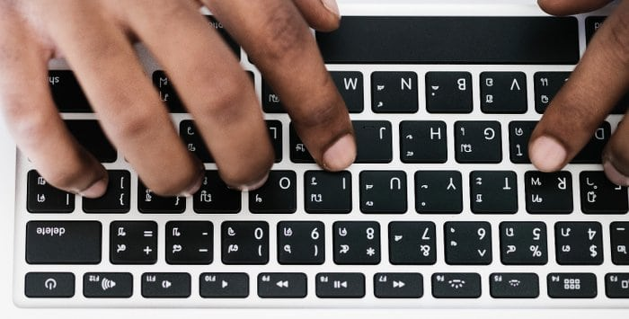 Hands using top row typing keys